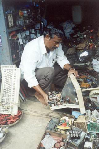 Picture showing a man working on electronic waste